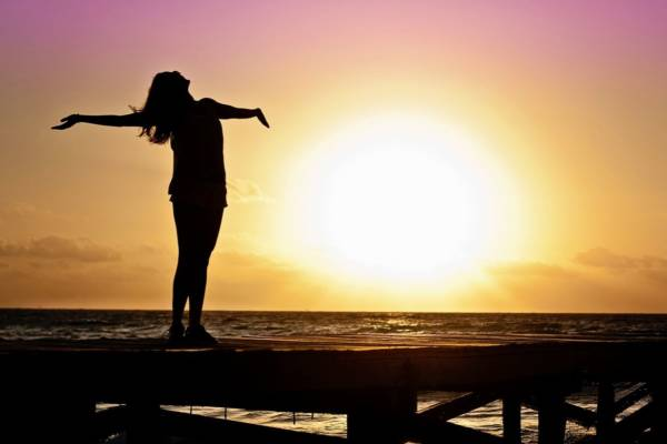 kobieta nad morzem o zachodzie słońca