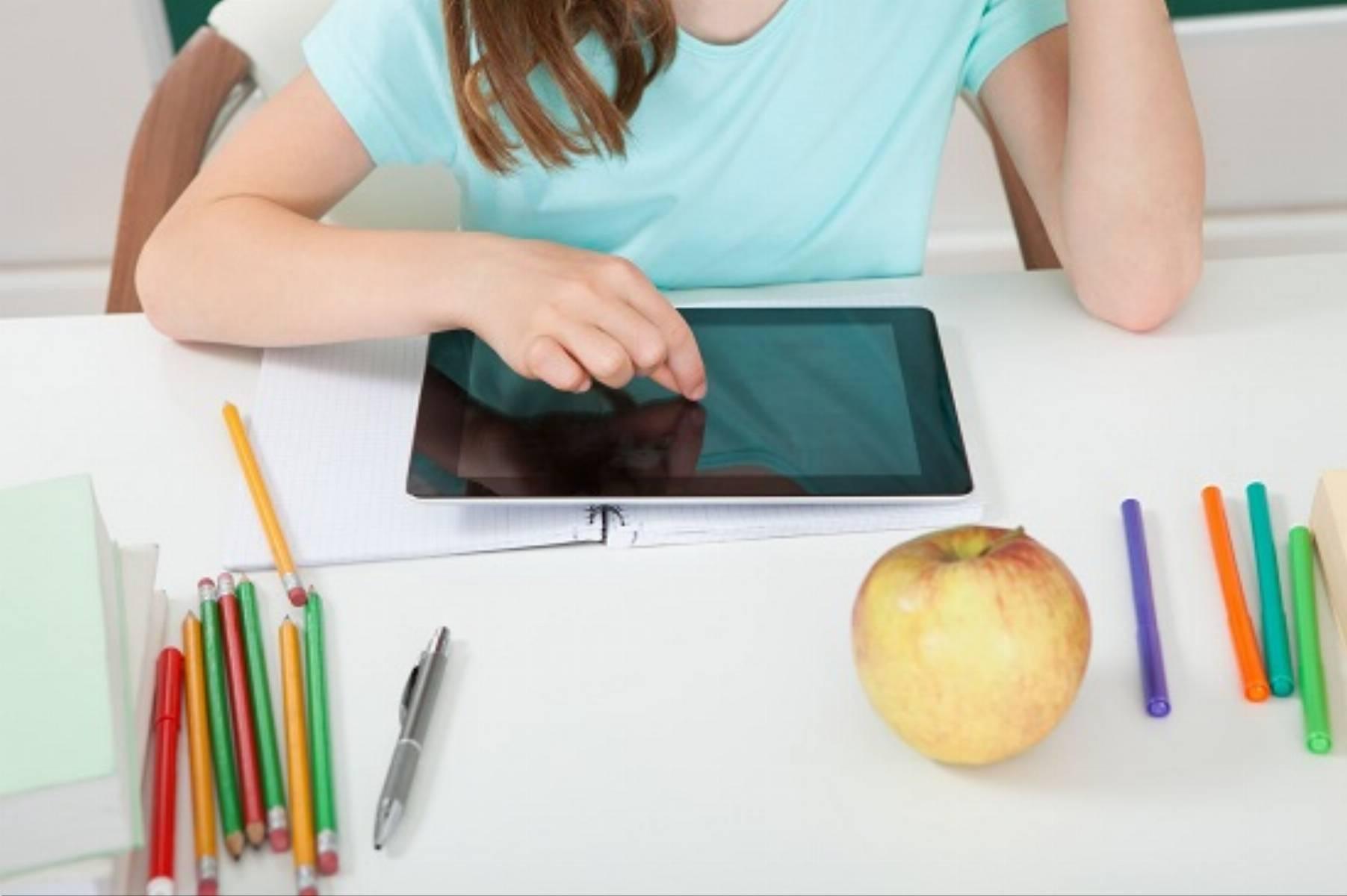 Schoolgirl Touching Digital Tablet At Table