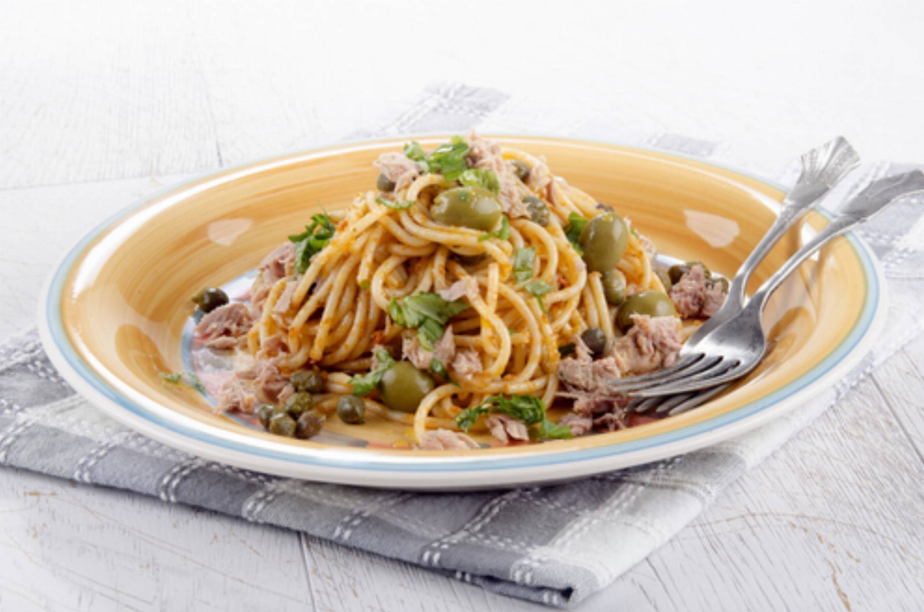 spaghetti with tuna, olive, caper and basil on a plate