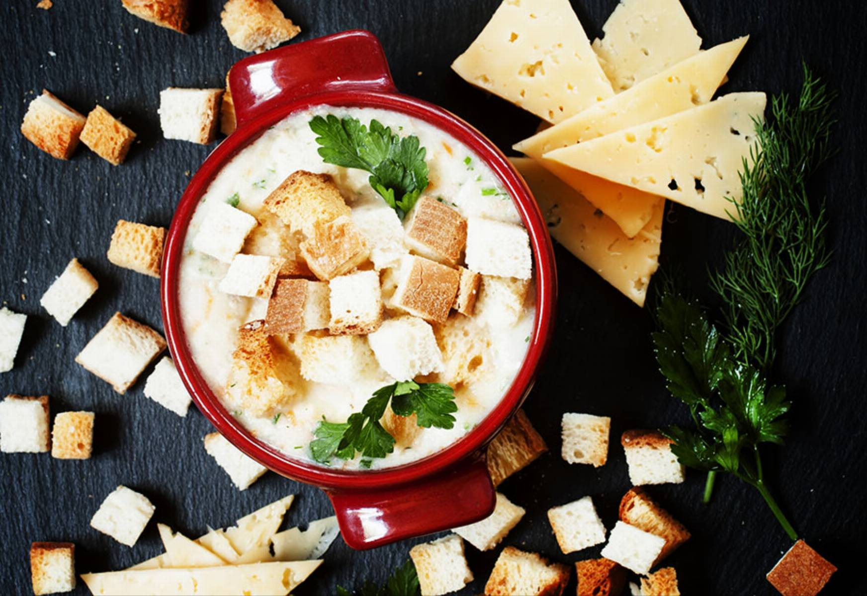 Cheese soup with croutons in red portioned saucepan, top view