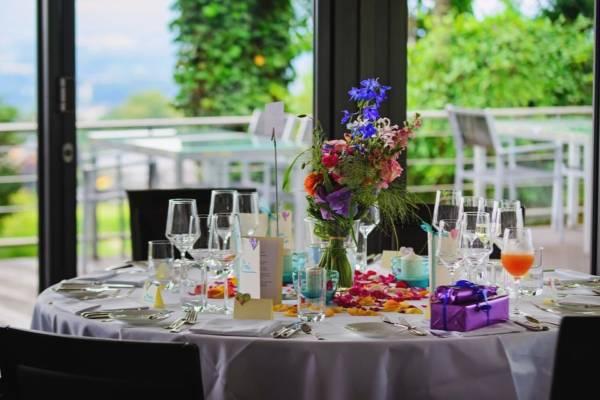 zastawiony stół i bukiety kwiatów